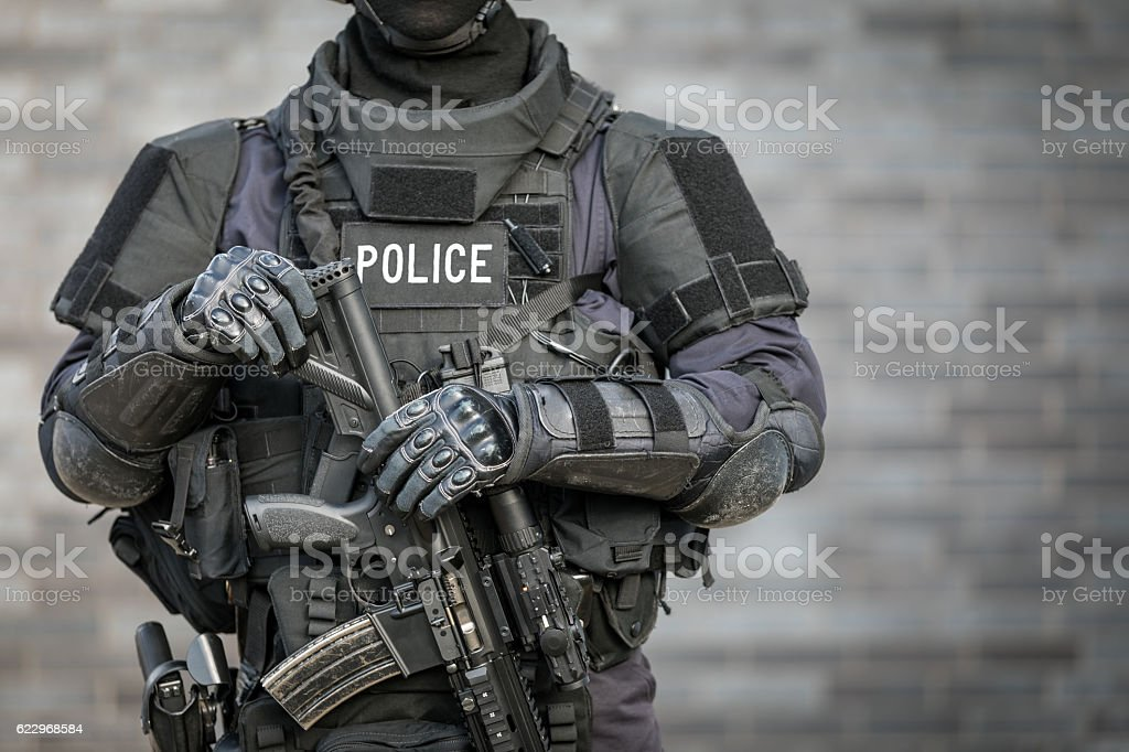 SWAT Police Officer Against Brick Wall - Photo