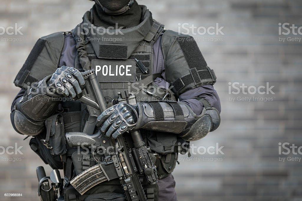 SWAT Police Officer Against Brick Wall - foto de acervo