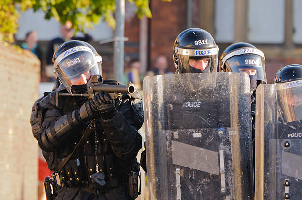 "Police officer aims AEP (plastic bullet) gun at rioters ""Belfast, UK - July 12, 2011: Police officer aims AEP (plastic bullet) gun at rioters during riots in Ardoyne"" riot police stock pictures, royalty-free photos & images"