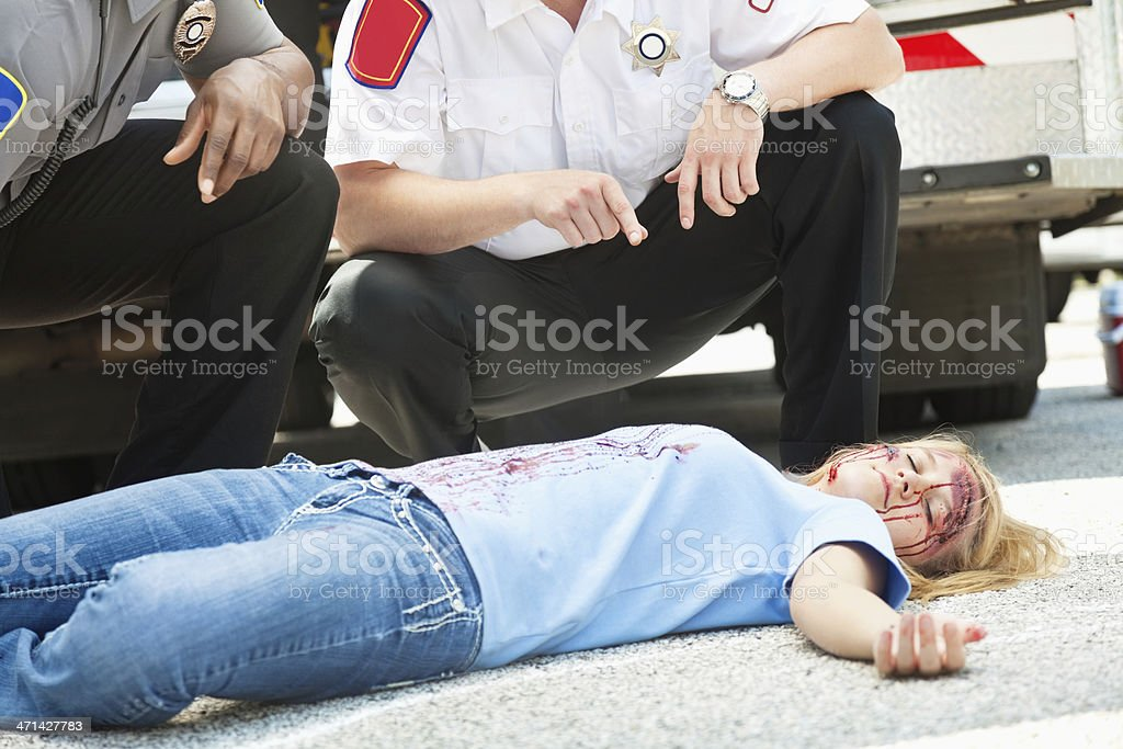 Police Officer and EMT examining body of accident victim stock photo
