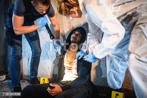 Low angle view of police officer and forensic scientist shining flashlight on murder victim leaning against wall and examining his bloody clothing.