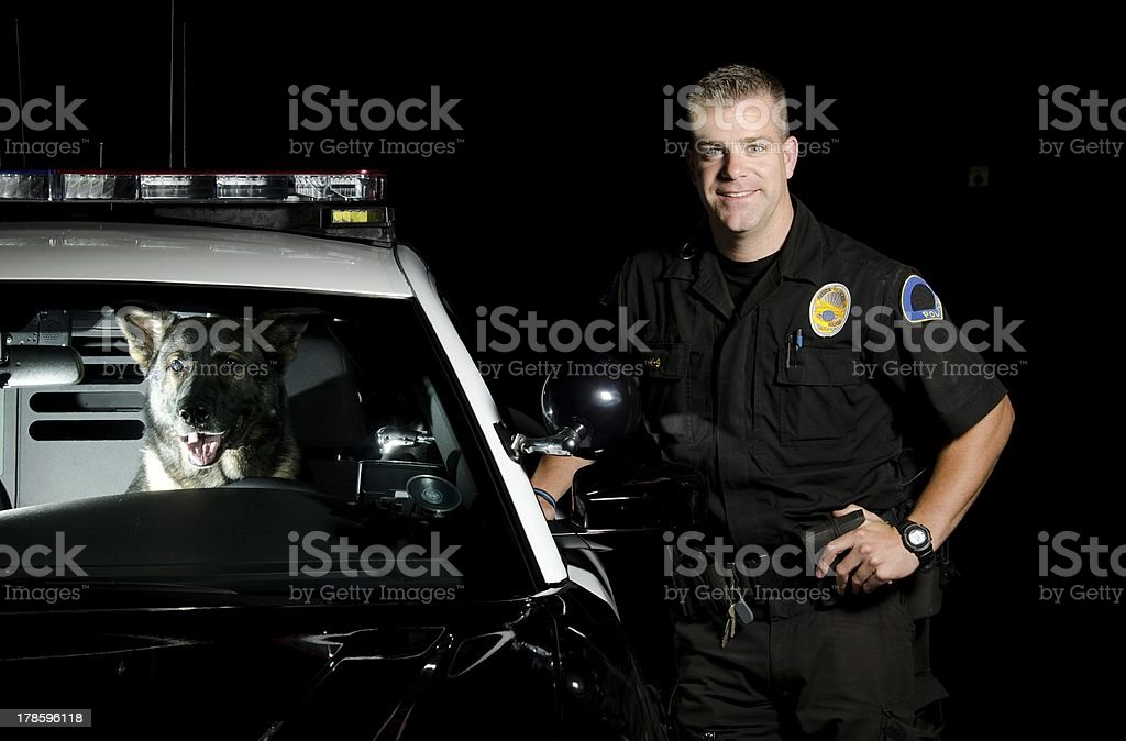 A police officer and his dog posing with a police car stock photo