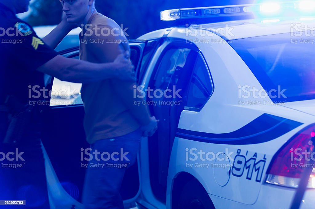 Police officer arresting a young man at night stock photo