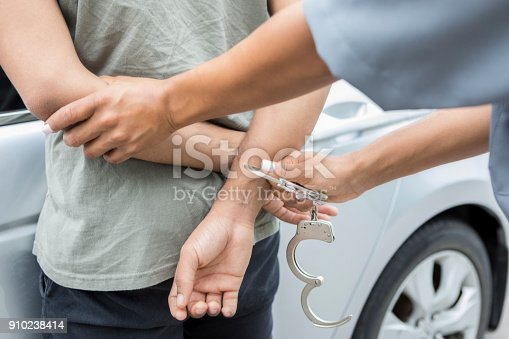 Unrecognizable police officer puts handcuffs on a man for drunk driving. The man is standing next to the car.