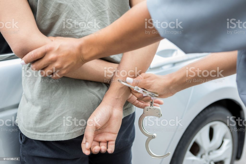 Police officer arrests young man stock photo