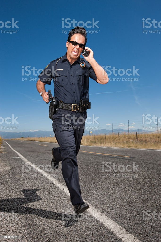 Police Officer Chasing Criminal on Roadway stock photo