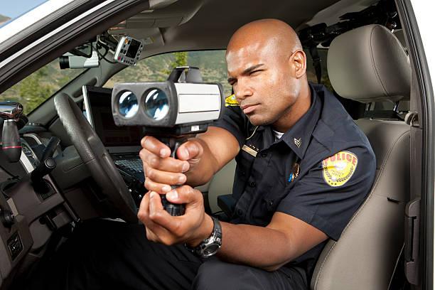 polizist, die fahrzeug-mit radar pistole - geschwindigkeitskontrolle stock-fotos und bilder