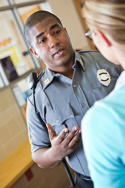 Police officer explaining something to school teacher Police officer explaining something to school teacher. police interview stock pictures, royalty-free photos & images