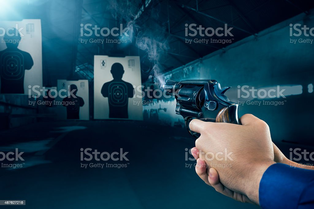 Police officer firing a gun at shooting range stock photo