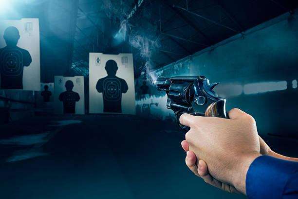 police officer firing a gun at shooting range - gun shooting stockfoto's en -beelden