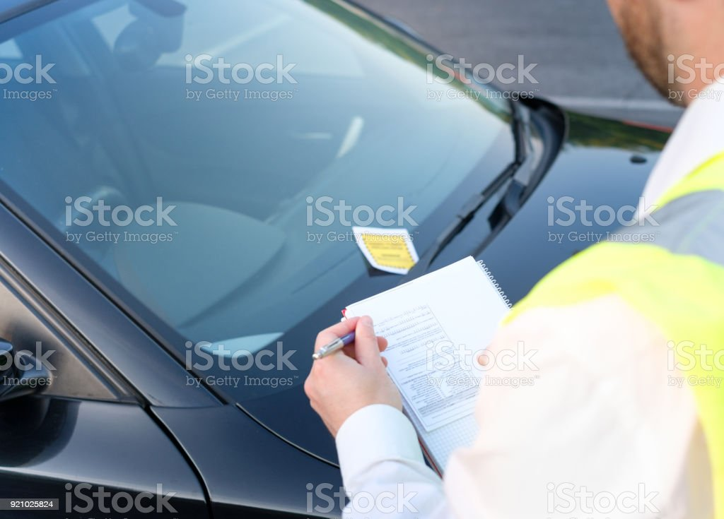 Police officer giving a fine for parking violation stock photo