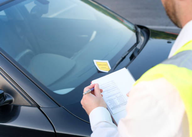Police officer giving a fine for parking violation Police officer giving a ticket fine for parking violation forbidden stock pictures, royalty-free photos & images