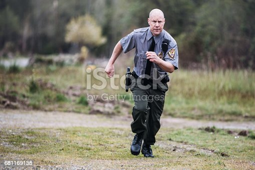 An on duty law enforcement officer, working hard at providing justice, keeping the peace, and making the country a safer place.  Here, the policeman runs to the scene of an emergency.