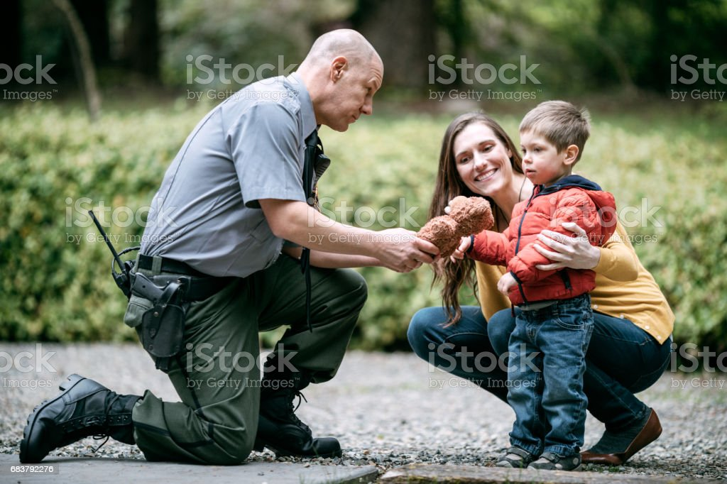 Police Officer Giving Child Stuffed Animal stock photo