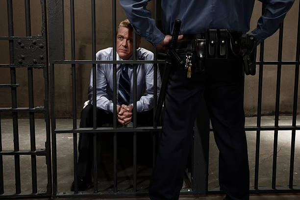 Police officer guarding man in prison cell, rear view, mid section stock photo