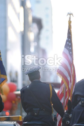 Police Officer holding American Flag - rear view with sun streaming in.