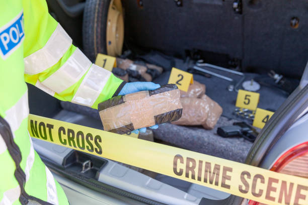 Police officer holding drug package discovered in the trunk of a car Crime scene - drug smuggling drug cartel stock pictures, royalty-free photos & images