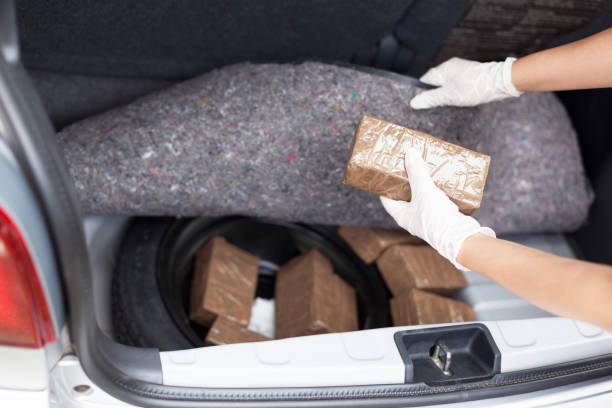 Police officer holding drug package discovered in the trunk of a car Drug bundles smuggled in a car trunk drug cartel stock pictures, royalty-free photos & images