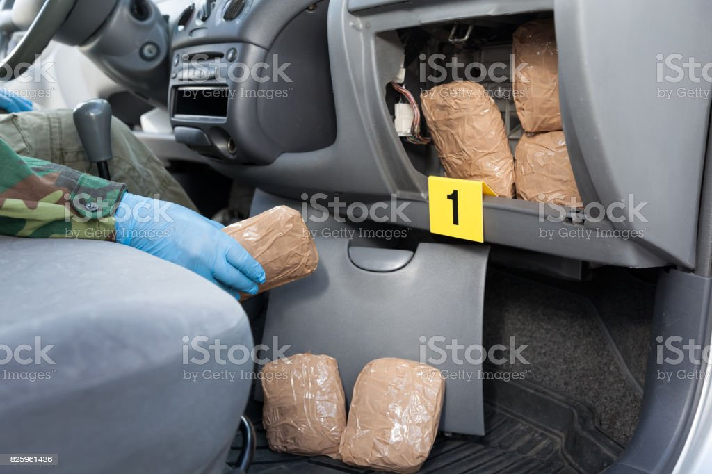 Police officer holding drug package found in secret compartment of a car royalty-free stock photo