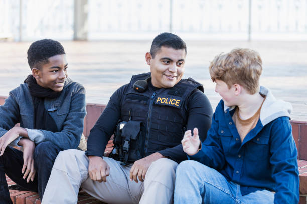 Police officer in community, sitting with two youths stock photo