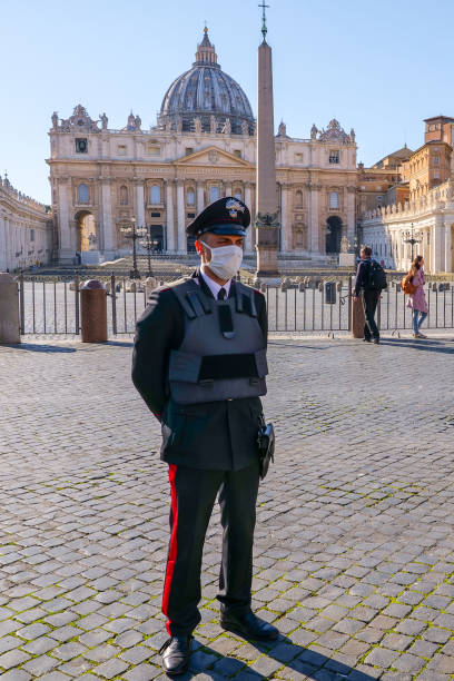 An Italian policeman with medical mask controls access to the square of St. Peter's Basilica stock photo