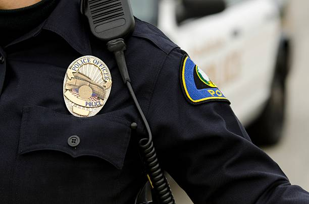 A police officer in uniform with a badge a close up of an officers uniform and badge with a patrol car in the background. police uniform stock pictures, royalty-free photos & images