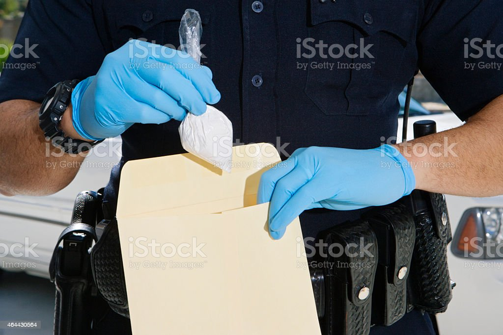 Police Officer Inserting Drug Packet In Envelope stock photo