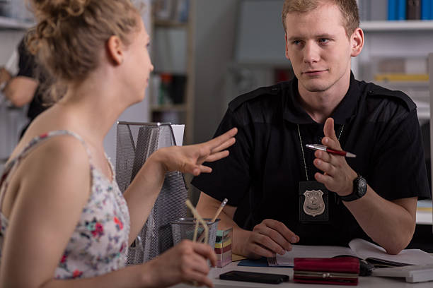 Police officer interrogating woman Police officer interrogating woman at police station police interview stock pictures, royalty-free photos & images