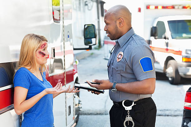 Police Officer Interviewing Witness at Accident Site Ambulance medic and police officer discussing accident scene.  police interview stock pictures, royalty-free photos & images
