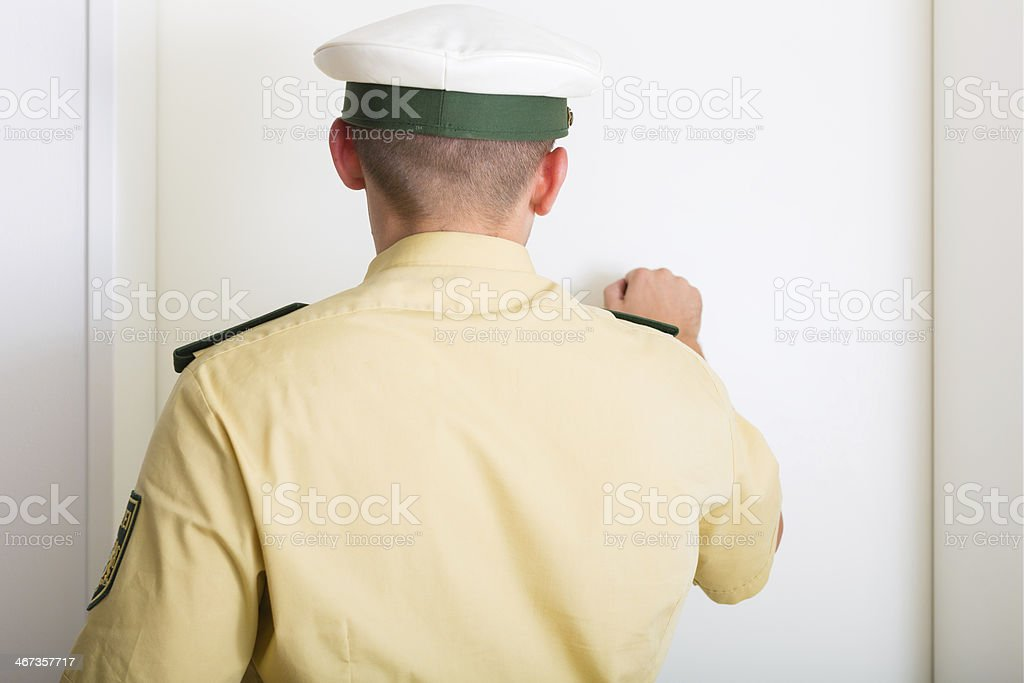 Police officer knocking on front door of home stock photo