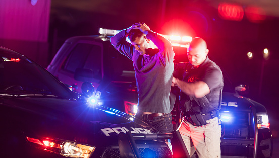 A police officer making an arrest, standing outside his patrol car at night, emergency lights flashing. The criminal is a young man in his 20s, standing his his hands on his head as the officer searches him.