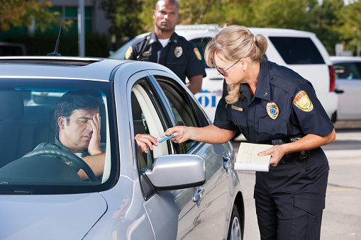 A mature female law enforcement officer stands by a vehicle she has stopped and takes the driver's license from a middle aged man while her partner stands by in the background.