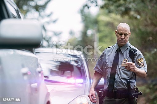 An on duty law enforcement officer, working hard at providing justice, keeping the peace, and making the country a safer place.  Here he inspects the drivers license of a person he has pulled over for speeding following checking their information in his patrol car.