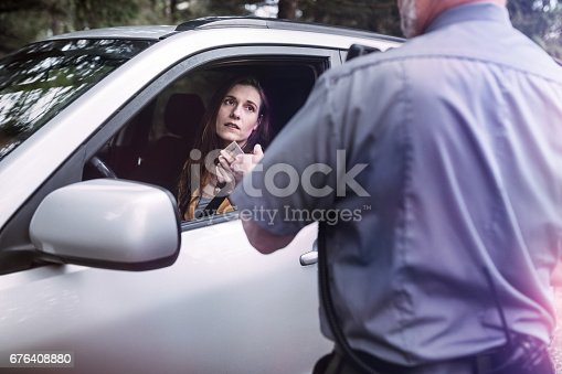 An on duty law enforcement officer, working hard at providing justice, keeping the peace, and making the country a safer place.  Here he inspects the drivers license of a person he has pulled over for speeding, given them a stern warning about the risk and danger of their behavior and the cost of a potential ticket.