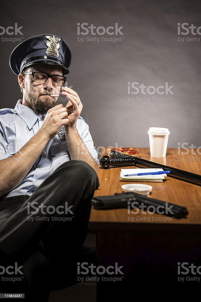 Police Officer on Break Lighting a Cigarette royalty-free stock photo