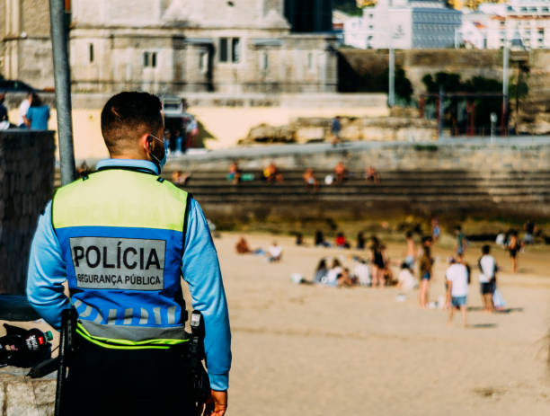 Police officer on vigilance next to a beach to ensure respect for social distancing during the Coronavirus Covid-19 epidemic in Portugal stock photo