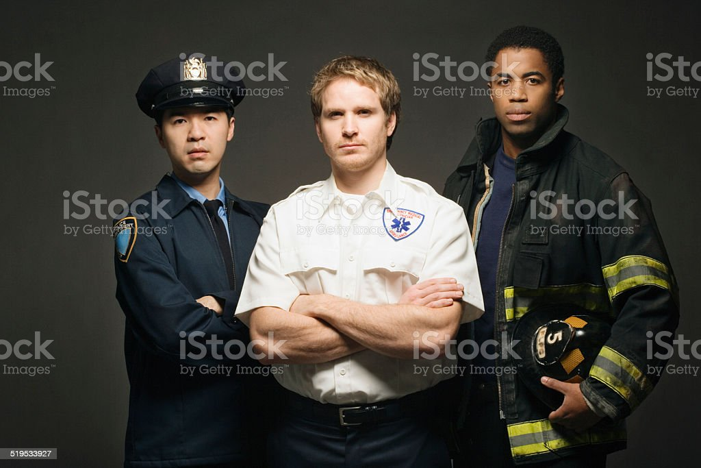 Police officer, paramedic, and fireman on black background, port stock photo