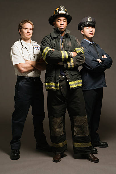 Police officer, paramedic and fireman, on black background, portrait stock photo
