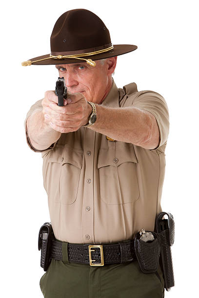 Police Officer Pointing Gun Photo of a mature law enforcement officer pointing a handgun directly at the viewer, isolated on a pure white background. trooper stock pictures, royalty-free photos & images