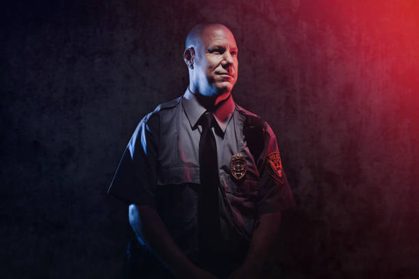Police Officer Portrait A portrait of a law enforcement officer, working hard at providing justice, keeping the peace, and making the country a safer place.  Shot in front of a concrete background, red and blue emergency lights illuminating their faces. police uniform stock pictures, royalty-free photos & images