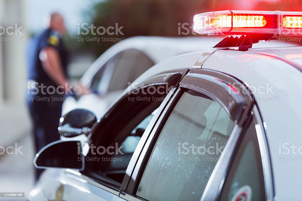 Police officer pulled over driver for traffic violation A police officer stands next to a car he pulled over for speeding,  reaching for the driver's ID.  The focus is on the police car in the foreground with lights on.  The policeman is out of focus in the background and unrecognizable. 2015 Stock Photo