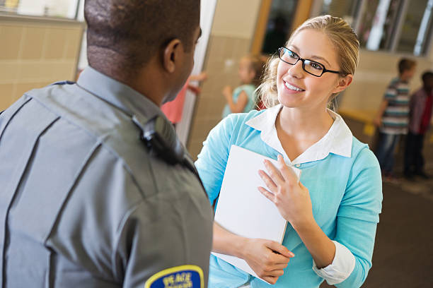 Police officer questioning friendly teacher in elementary school hallway Police officer questioning friendly teacher in elementary school hallway. police interview stock pictures, royalty-free photos & images