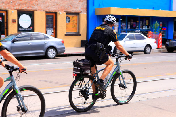 Police officer riding a bicycle along 4th Ave in Tucson AZ stock photo