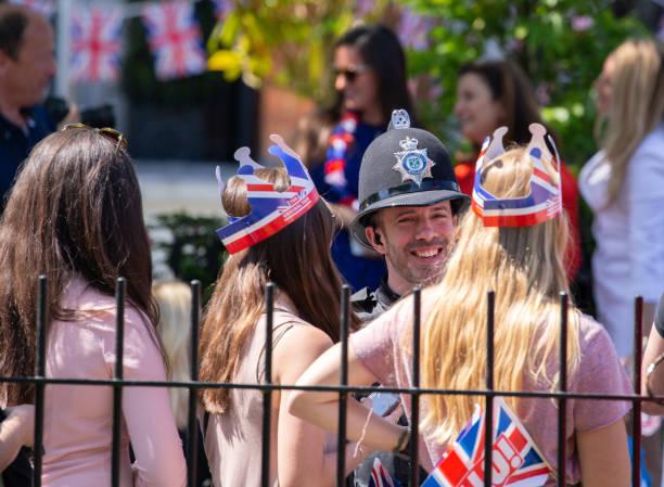 메 건 대 한 전문적인와 해리 왕자의 결혼을 축 하 하기 위해 윈저 그레이트 공원에서 사람들의 수집 군중와 농담을 공유 하는 경찰 - meghan markle 뉴스 사진 이미지