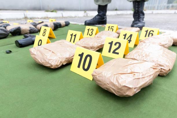 Polizist steht Wache über beschlagnahmten Pakete von Drogen – Foto