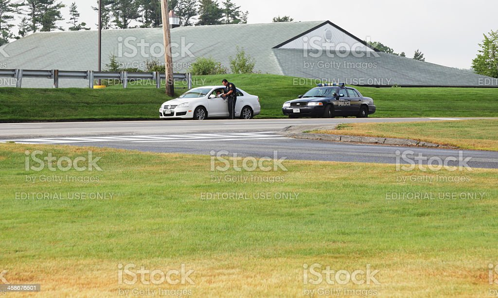 A police officer stands next to a car - stopped after a traffic...