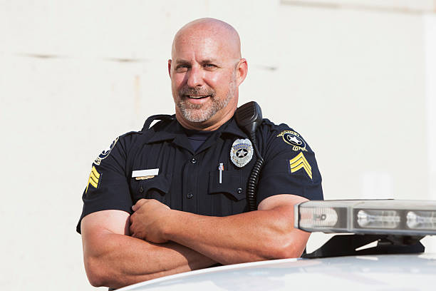 Police officer standing with arms crossed stock photo