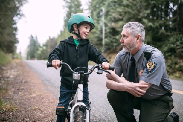 policjant rozmowy z dzieckiem na rowerze - policja zdjęcia i obrazy z banku zdjęć