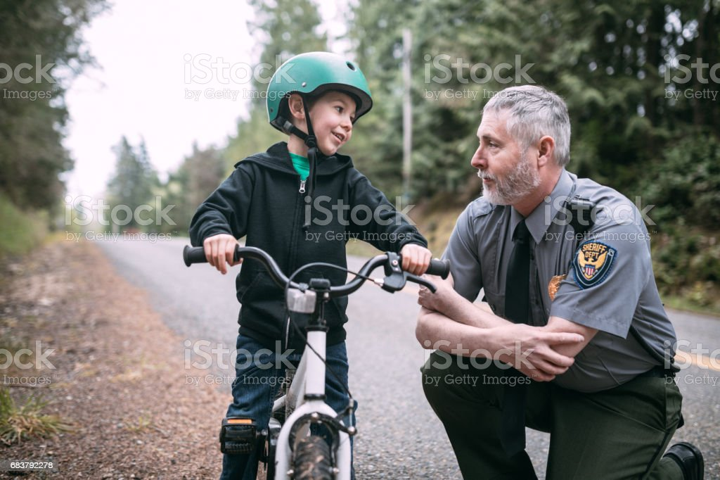Police Officer Talking to Child on Bike stock photo