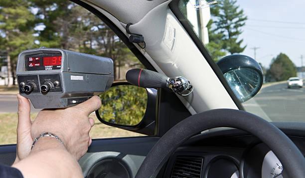 polizist mit einem handheld radar pistole - geschwindigkeitskontrolle stock-fotos und bilder